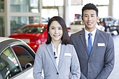 Confident salespeople standing with new cars in showroom