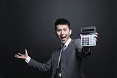 Excited businessman showing a calculator