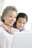 Chinese grandmother with grandaughter using a laptop