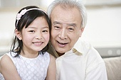 Portrait of grandfather and granddaughter at home