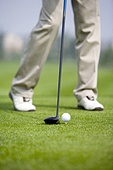 Close-up of golfer teeing off