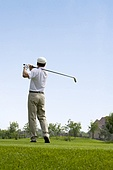 Male golfer swinging club