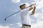 Male golfer swinging club