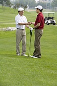 Two golfers shaking hands on the course