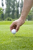 Close-up of putting a golf ball on tee