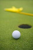 Close-up of golf ball by hole