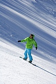 Young man snowboarding down a ski slope