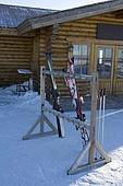 Ski equipment outside a log cabin