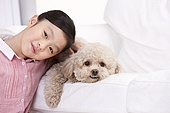 Little girl playing with a pet toy poodle
