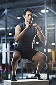 Young man doing box jump in crossfit gym