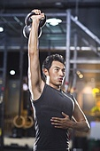 Young man training with kettlebell in crossfit gym