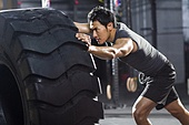 Young man pushing large tire in crossfit gym