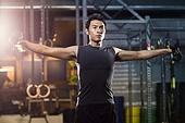 Young man lifting weights at gym