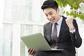 Young businessman with laptop punching the air with excitement outdoors