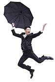 Fashionable businessman jumping in mid-air with umbrella in hand