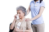 Female nursing worker comforting weeping senior woman