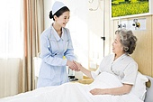 Nurse taking care of senior woman in hospital