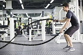 Young man exercising with battling rope at gym