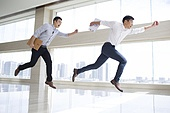 Young businessmen running in office building