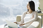 Young woman using laptop on couch