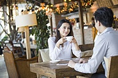 Young woman and man talking in cafe