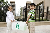 Boy and girl holding recycling box