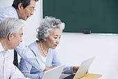 Senior adults having computer class at school