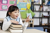 Young student holding books in classroom