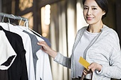 Mature woman with credit card in clothing store