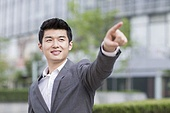 Young businessman pointing to the distance