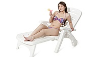 Young woman in bikini relaxing on sand chair