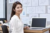 Designer sitting before laptop in studio
