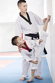 Young instructor teaching boy Tae Kwon Do