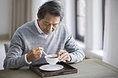 Senior man eating nutritious porridge