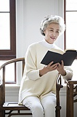 Happy senior woman reading a book