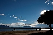People at a lakes edge with a mountain range in the background