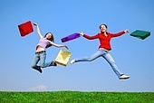 Girls jumping with bags against blue sky
