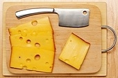 Swiss cheese and knife on board