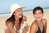 Mother spreading sunscreen on her daughter's shoulders