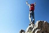 Climber reaches his arms up, standing on a stone at the top of his route, over a deep blue sky.