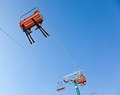 Skiers are riding in chairlift in a ski area, low angle view, Italy. Large copy-space at the top.