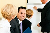 Business team receiving a presentation held by a male co-worker standing in front of a flipchart