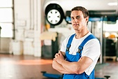 Auto mechanic standing in his workshop in front of a car on a hoist