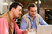 Two friends in Bavarian pub in traditional clothes sitting on a table in a pub with laptop