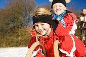 Two little children with their toboggan at the top of a hill in the snow waiting to start the fun