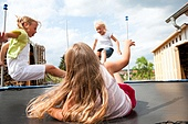 Three children jumping on a trampoline in front of their home