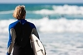 Young surfer on the beach with his surf board beside, looking at the ocean for the best waves