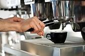 Barista prepares espresso in his coffeeshop; close-up