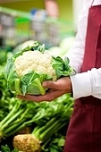 Man - only hands to be seen - in supermarket as shop assistant; he is carrying a cauliflower