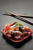 A close-up of chopsticks and a square plate with two pieces of eel nigiri, wasabi and ginger.